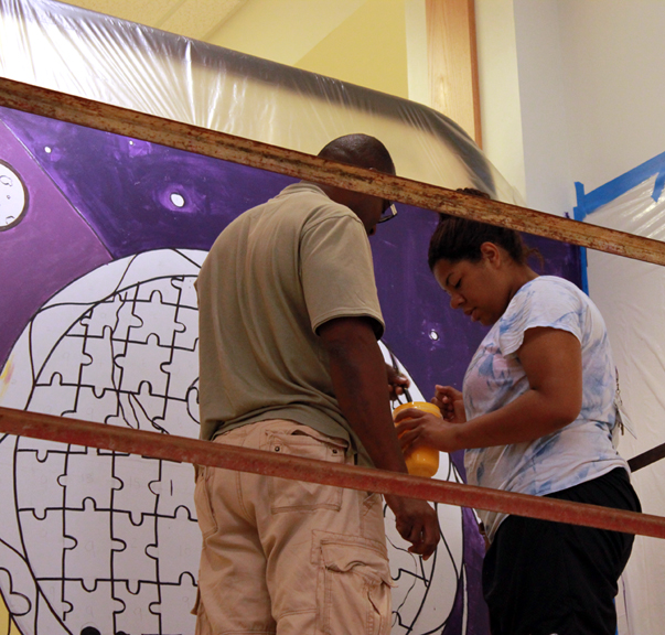 Chris Emmanuel and a student working on the Diversity Mural