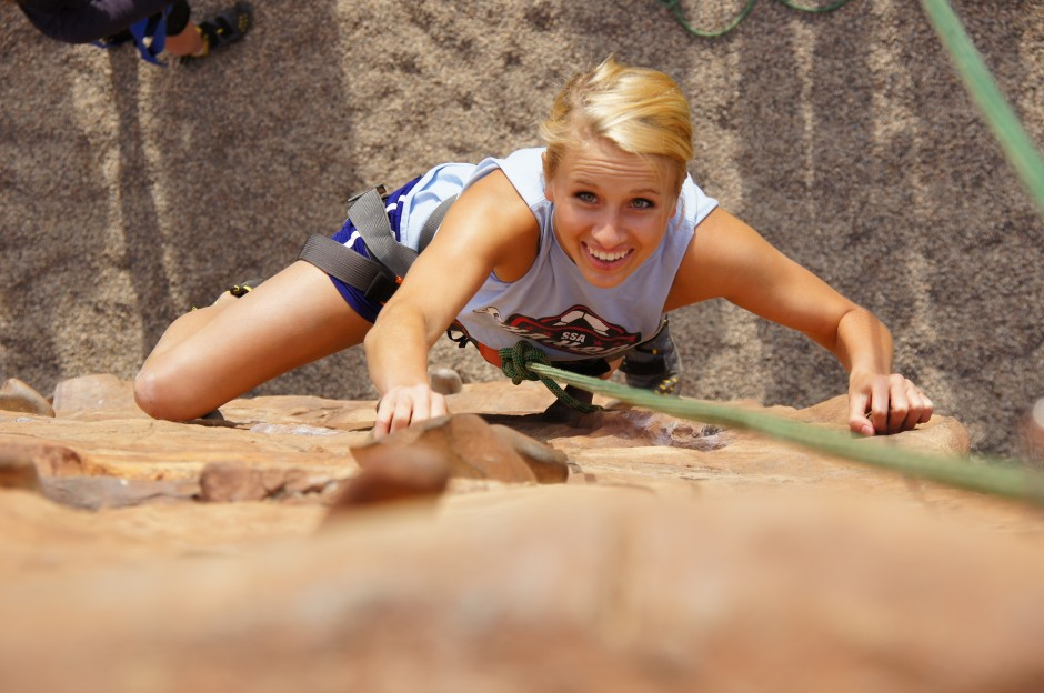 A woman climbing up the outdoor climbing wall.