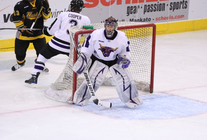 Austin Lee as the goalie in a hockey game against the Michigan Tech Huskies