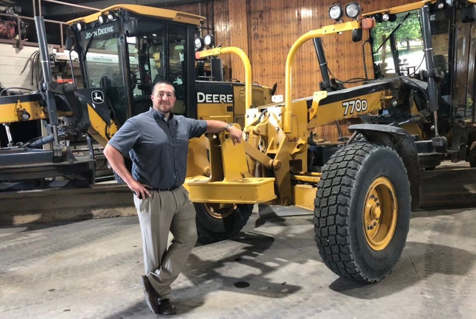 Ryan Thilges stands next to a John Deere paver tractor.
